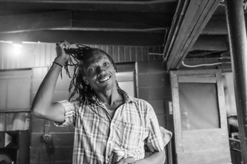 A Jamaican farm worker lets his hair down and is ready to enjoy an evening of food and music at his camp in Upstate NY