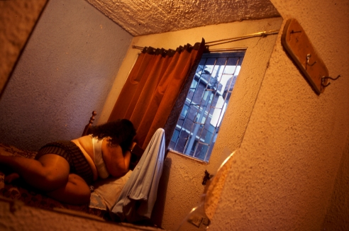 A prostitute looking thru the window of her work place in the center of the city, Bogota Colombia,