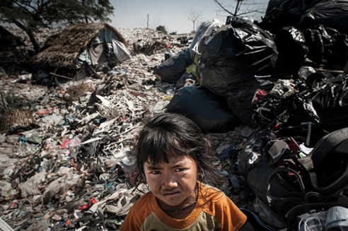Mae Sot, Thailand; February 2014. A young burmese girl reads a book in the middle of a garbage dump.