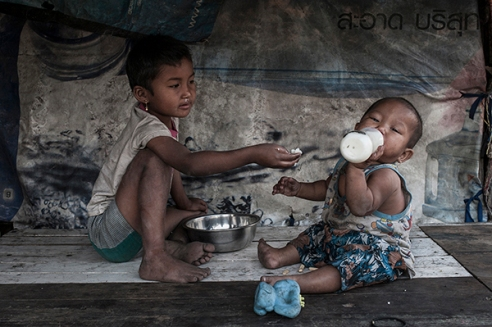 . Mae Sot, Thailand; February 2014. Two Burmese children eat in the slums of the landfill.