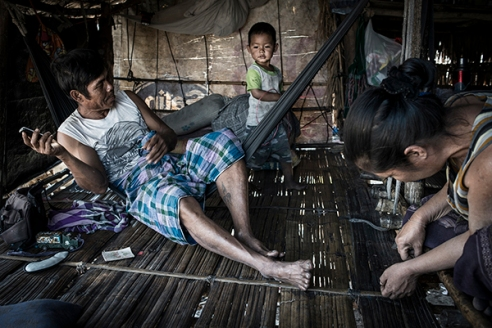 Mae Sot, Thailand; February 2014. A family of Burmese migrants rests in his shack