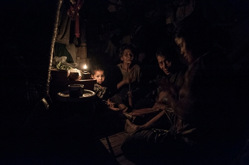 Mae Sot, Thailand; February 2014. A family of Burmese migrants dine with the help of candlelight.