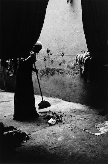 A Bedouin girl cleans up after the camels. (Kafrat al Jabal, Giza, Egypt)