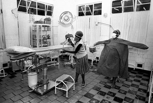Medical assistants at the Ankoro Hospital in Zaire prepare for an emergency operation for a woman who was carried several miles on a stretcher to the hospital after a botched attempt at delivering her baby left the child dead, and the woman's life in jeopardy. 1987.