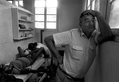 Dr. Andreas Steiner takes a break during a procedure to treat a woman who had recently experienced a miscarriage, which she attributed to witchcraft. Steiner ran a medical operation for an NGO in the Shaba Province of Zaire (Congo) during the late 1980s.