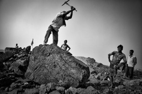 Men at work breaking pieces of coal.