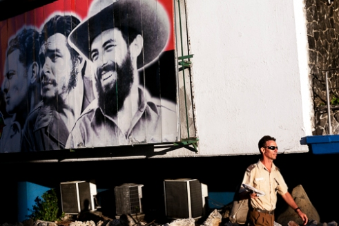 A soldier walks beneath a mural of Camilo Cienfuegos and el Che in La Habana.