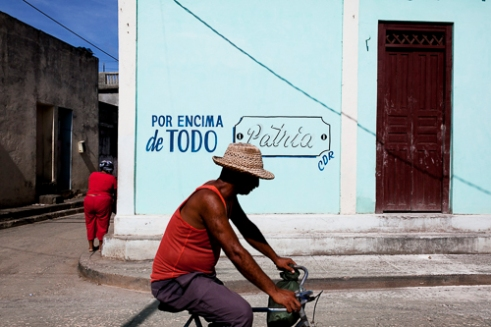 A man travels by bike downtown Baracoa . The revolutionary murals are typical in Cuba .