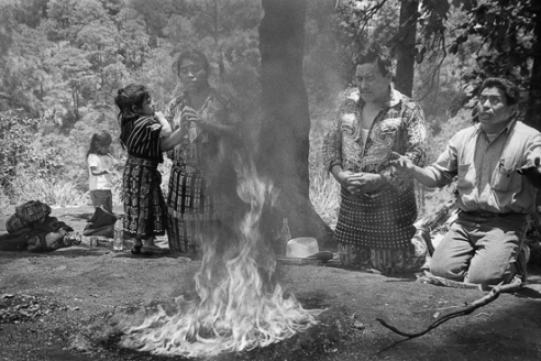 Family prays before the sacrificial fire at Pascual Abaj. Chichicastanengo, Guatemala