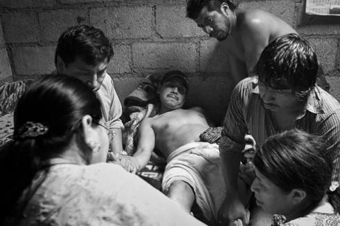 Berta Navichoc, healing Pedro Pablo Mendoza, who is surrounded by his family. Santiago Atitlán, Guatemala