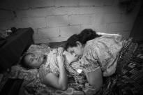 Healer and midwife Josefina Vazquez de Gonzalez examining a pregnant woman.  San Pedro La Laguna, Guatemala