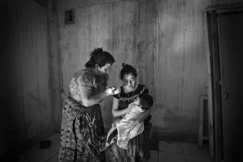Josefina Vazquez de Gonzalez, healer, giving an herbal remedy to baby Yaretzi Quiacin Tzunúo. San Pedro La Laguna, Guatemala