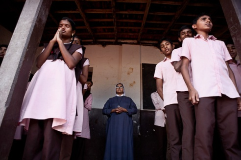 """Children of the 9th Standard class at the Roman Catholic High School, undertake the daily pledge for education during the morning assembly. The state of Kerala passed in 2002 """"The Right to Education Act"""" where all children between the age of 6 years and 14 years must be in full time education. Although the population is split 50% Hindu, 25% Christian and 25% Muslim most children, regardless of their religion are taught together."""