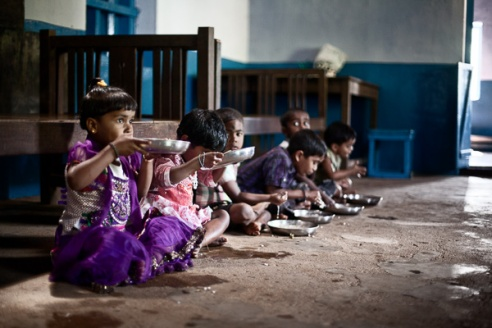 The children of the estate run nursery sit on the floor to eat their lunch. The children at the nursery are provided with both a morning snack and lunch during the day as the majority of the parents' work from 8am to 4:30pm, six days a week regardless of weather.