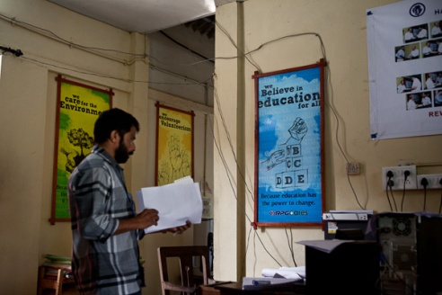 An office worker stands in front of welfare posters which advocates the companies underpinning of education. The new generation are 93% literate, as opposed to 30% in the 1950's, and with children having aspirations for employment outside the industry, especially women. The promotion and funding of education has created difficulties for the company who will face a severe labour shortage in the next 10 years, which in the future may only be solved by either using migrant workers or mechanization.