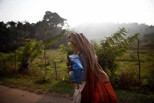 Bavani (39 years) makes her way home after a days work in the fields. The women work on extremely humid conditions with temperatures usually in the high 30 degrees Celsius. Their clothing is to protect their head from the weather and also protect their backs from the heavy loads they have to carry during the day.
