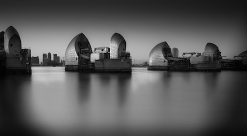 My City Protector The Thames barrier protecting the greatest city in the world, London. The light shining off the barrier and shimmering in the strong city waters of The Thames. In the distance you can see the impressive buildings of the city that the barrier protects.