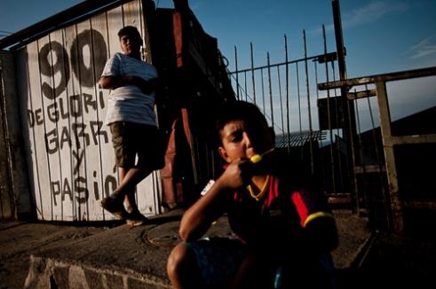 Niños juegan y comparte una tarde en Cerro El Litre, Valparaíso. Atrás, un mural referente al equipo de fútbol, Colo - Colo, el más popular de Chile. Children playing during a afternoon in Cerro El Litre, Valparaiso, Chile