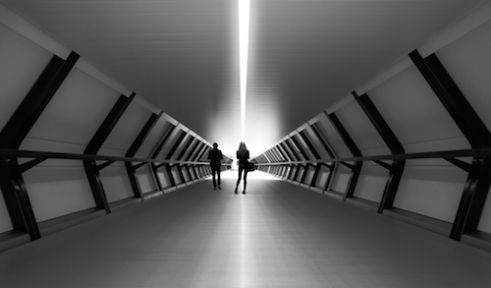 To find another race The space age tunnel leading to the new cross rail in London. A very futuristic looking tunnel in the city of London, the woman standing braking the beam of light that looks like it would go on forever.