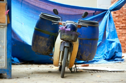 Containers carrying construction waste are attached to motorcycles.