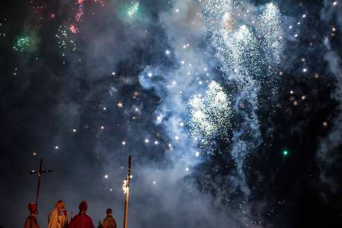 At the fireworks display, the Archbishop gives a speech, accompanied by his retinue, while members of the crowd throw bangers and firecrackers at them.