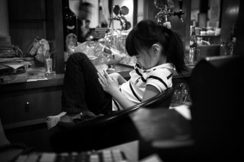 CHINATOWN. A little girl play with her phone in a restaurant.