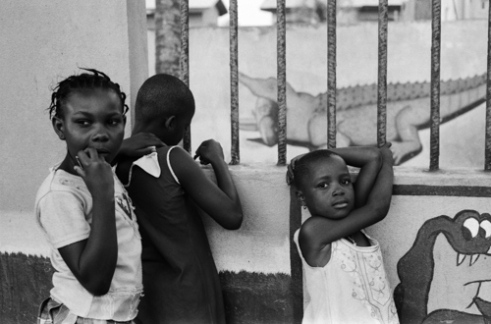 Predators These young girls are only a few meters away from the most frightening predator from African nature. But here, in the tax free zone of Lomé, the crocodile they are trying to awake is really harmless behind the bars. In the capital, the most dangerous predators are free. Are they the Green Army suited black men sitting on a throne in their government palace, or are they suited white men in western embassies, or multinational companies taking profits from the tax free zone.