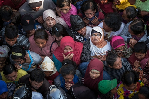 SEMARANG-INDONESIA, September 24, 2015. Thousands of Indonesian Muslims queue to get a share of the sacrificial meat during celebrations of Eid al-Adha at Kauman Mosque, Semarang City. The committee distributed 6,800 packages of sacrificial meat to the residents. Muslims worldwide celebrate Eid Al-Adha, to commemorate the Prophet Ibrahim's readiness to sacrifice his son as a sign of his obedience to God. Permissible animals such as goats, sheep, and cows are sacrificed.
