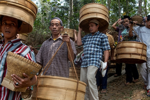 """TEMANGGUNG-INDONESIA, October 24th, 2015. Javanese Muslim people gathered to hold """"Sadran Desa"""" and to commemorate The holy month of Muharram or """"Suro"""" at Tlogopucang Village, District of Temanggung Central Java, Indonesia. Villagers bring the bamboo bucket full of food called """"Tenong"""" as the result from their crops this year in the sacred hills and pray together, thankful to God for getting more blessing in their life."""