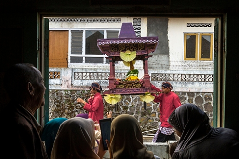 """KOPENG-INDONESIA. November 29th, 2015. Villagers watching the parade inside their home. Javanese people gather to hold a thanksgiving called """"Saparan"""" to say thanks to God as their massive harvest result this year at Kopeng village, District of Semarang Central Java Indonesia. By bringing the symbol of a mountain full of food and crops they parade around the village with typical costumes and performs traditional dance."""