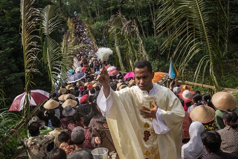 MAGELANG-INDONESIA. December 25th 2015. One of priest from Church of Santo Paulus spread the holy water to the villagers on the bridge. Hundreds of Catholic villager whom living on the slopes of the mountain of Merapi gathered on Kalilamat bridge, Ngargomulyo village, District of Magelang Central Java, Indonesia, for held Christmas Mass. Most of them are a farmer, and brought their harvest this year as the symbol to thankful and preserving nature on the slopes of Mount Merapi.
