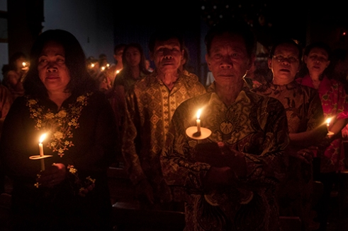 HARJOSARI-INDONESIA. January 14th, 2016. Hundreds catholics villager on Harjosari Village, Semarang District, Central Java, Indonesia gather at the ST Maria Assumpta Church to hold a torch cross parade and mass pray, an annual event for praying at the beginning of 2016. In this event they bring candles as a symbol of grief to pray together and giving sympathy for terror attack which happened in Jakarta, the capital city of Indonesia. They pray and hope Indonesia will be more peaceful in the beginning of a year and no more terror attack