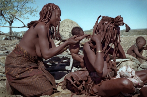 Mukaandjoao helps Kakaendona to attach Tjimbosi, her newbord, to her calf leather baby carrier. oHere, Kunene North Region, Namibia, 1998