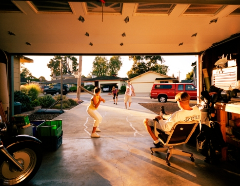 Samantha, Redwood City, California. Father watches as wife and children play baseball in the driveway and street.
