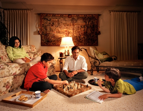 Anniqua, Redwood City, California. An immigrant family enjoys a quiet evening (without electronics) in their living room. The mother reads, the father and oldest son play chess, and the younger son reads a children's Koran.