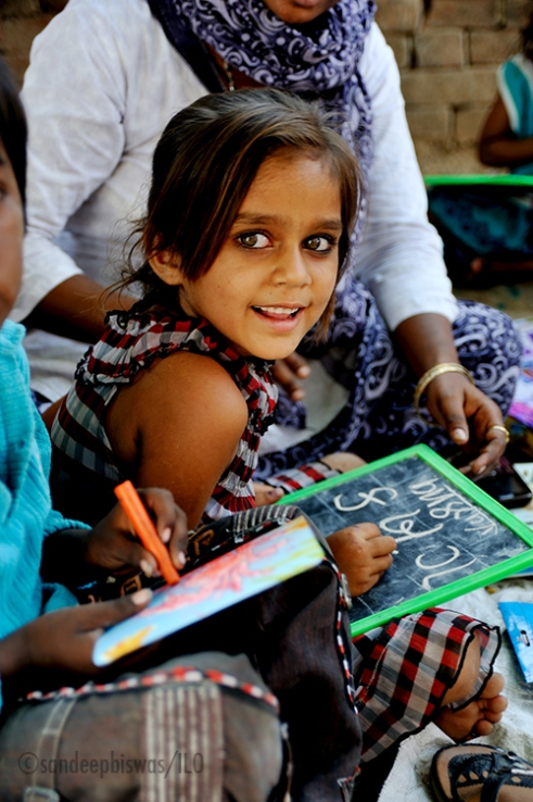 Education Resource Center, Sai Baba Nagar, Vadodara, Gujarat, India: A young girl is learning to write letters in Gujarati at the ERC. These ERC's duplicate as schools as there are no proper schools in the area. These ERC's are either tiny rooms or open spaces in the slum clusters. Children are taught various activities through various education and learning methods directed by the local government. Photo credit: Sandeep Biswas/ILO