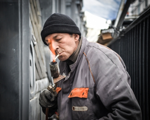 Worker lighting up a cigarette with materials in hand.