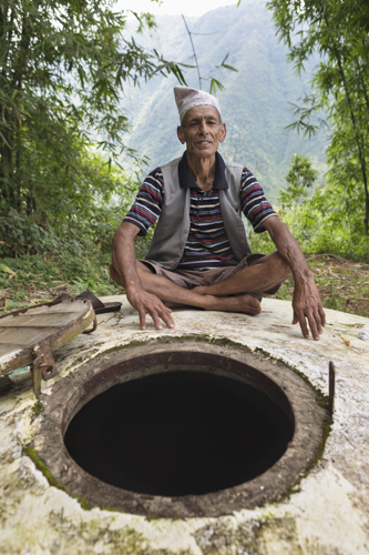 Farmer Dilli Ram Regmi sits proud beside the well that is filled with water powered by solar water pumps at the base of the mountain in Sirubari, rural Nepal. This storage well has proved highly beneficial to the farming community who would otherwise have to walk hours to carry drinking water daily.