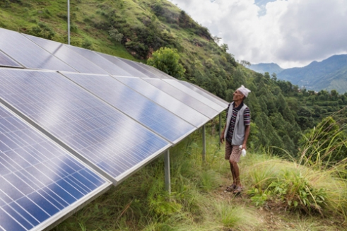 Farmer Dilli Ram Regmi stands beside the 4.5kW solar array that harnesses the sun's energy to pump water for drinking and mushroom farming in his community in rural Sirubari, Nepal.