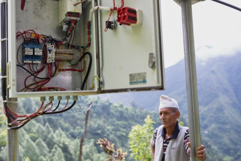Farmer Dilli Ram Regmi shares the interior of the controller for the solar water pumping system that pumps water over 80m high for drinking and agricultural purposes in his community in Sirubari, Nepal.