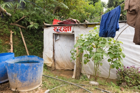 """Farmer Dilli Ram Regmi and his family are forced to reside in this temporary shelter with the word """"Safety"""" printed above the entrance in Sirubari, rural Nepal. Their home was damaged and cracked as a result of the April 25th earthquake that hit the country."""