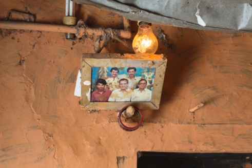An old family photograph of farmer Dilli Ram Regmi and his farmers group inside the bedroom of his cracked house post earthquake in Sirubari, rural Nepal.
