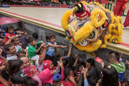 Lion Dance in Sam Poo Kong Temple SEMARANG-INDONESIA, February 19 2015. Crowds gathered in Sam Poo Kong Temple in Central Java to celebrate the arrival the Chinese New Year. The occasion was marked with a lion dance, called 'Barongsai' in Indonesia, which is now performed openly after a government ban of the custom ended in 1998. Many in attendance crowded around the lions, lifting children up to place offerings in their mouths, in the hope of bringing blessings for the lunar year of 2566.