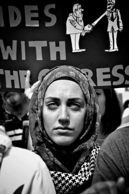 A Palestinian women observe Activists rallying supporters to march through Chicago streets, during the Protest Against Israel and Free Gaza Protest in the summer of 2014. Chicago, IL. 2014