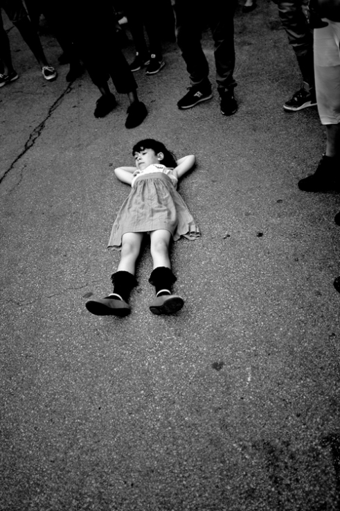 A little girl lies on the ground as a band preforms during Pilsen's first food truck festival in Chicago, IL. 2015. Chicago, IL