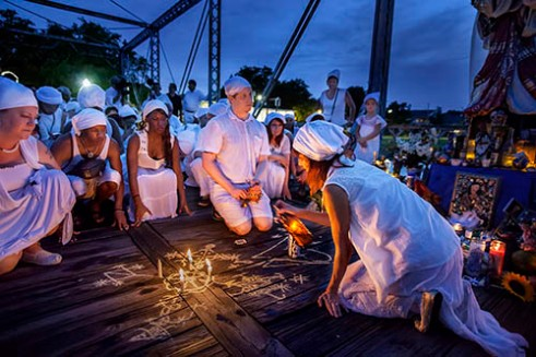 St John's Eve on the Bayou 2015 NEW ORLEANS, LA. Vodou Priestess Sallie Ann Glassman pours holy water over a veve as the Vodouisant around her pray . Veve are Vodou symbols drawn with cornmeal as part of a ritual to honor Marie Laveau. Her group, La Source Ancienne Ounfo, is a private Vodou society that works with the spirits of Haitian LWA.