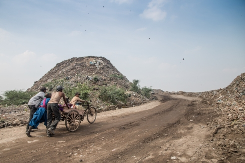 A family getting their cycle rikshaw up on top of the Okhla Landfill - Delhi.