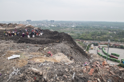 Scavengers are seen on top of the landfill as the line of Delhi Transport Corporation Bus Depot is seen far below.
