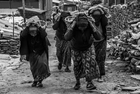 Women strap baskets to their foreheads to carry building rocks. Barpak