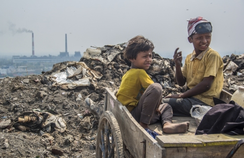 Children waiting as their parents scavenged in the municipal waste in Okhla Landfill - Delhi.